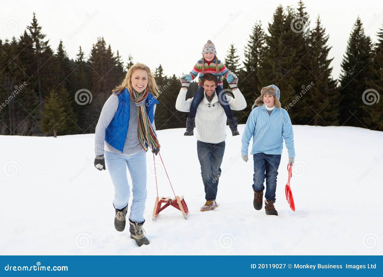 Familia joven que recorre a través de nieve con el trineo