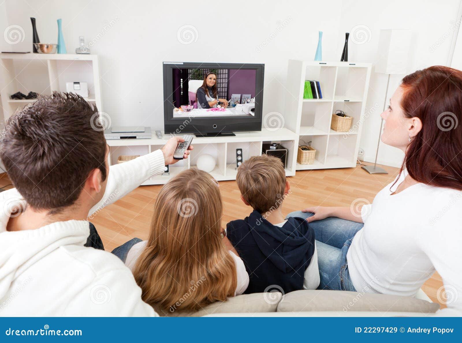 Familia joven que ve la TV en el país