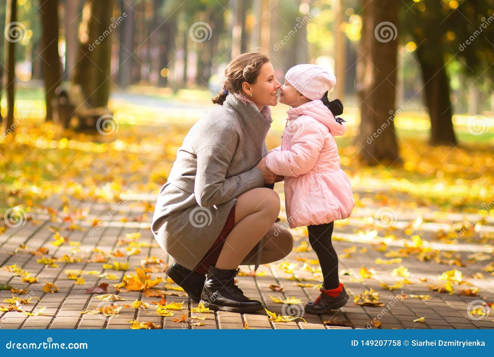 Familia Madre e hija en parque del oto?o Madre con el ni?o en al aire libre