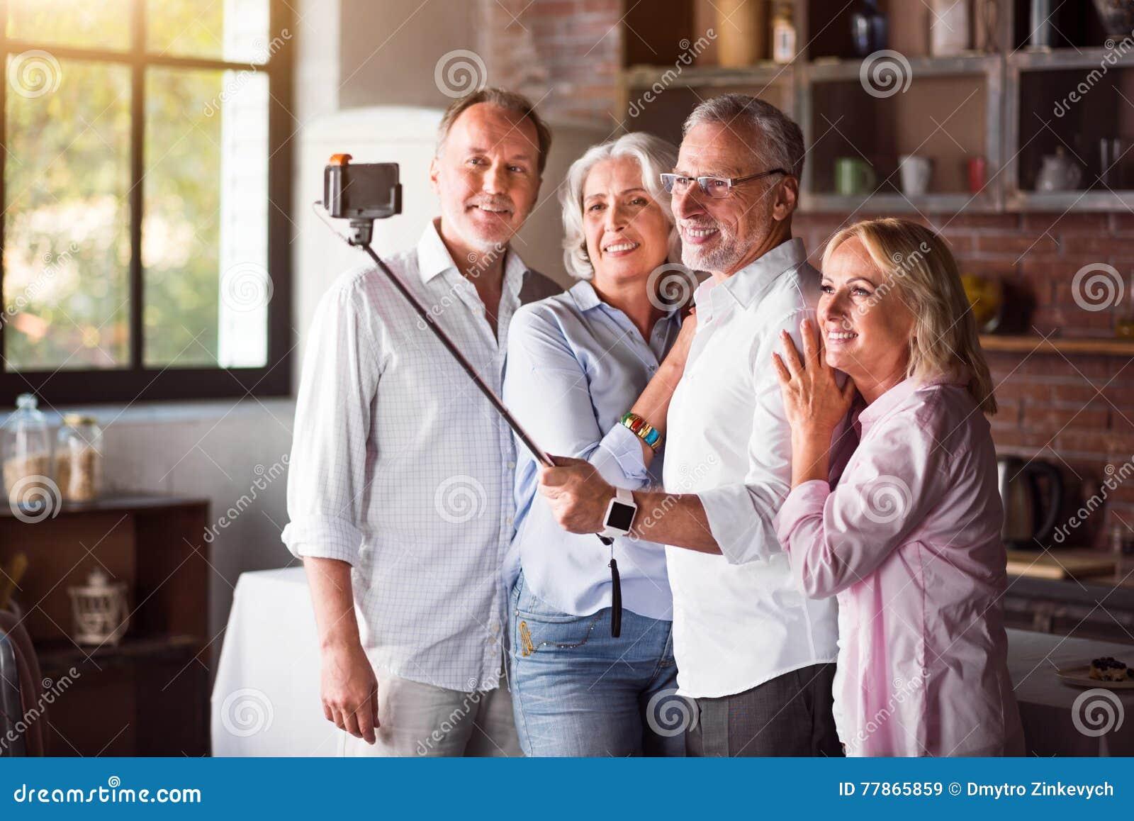 Familia madura feliz que toma selfies con smartphone en la for Maduras en la cocina