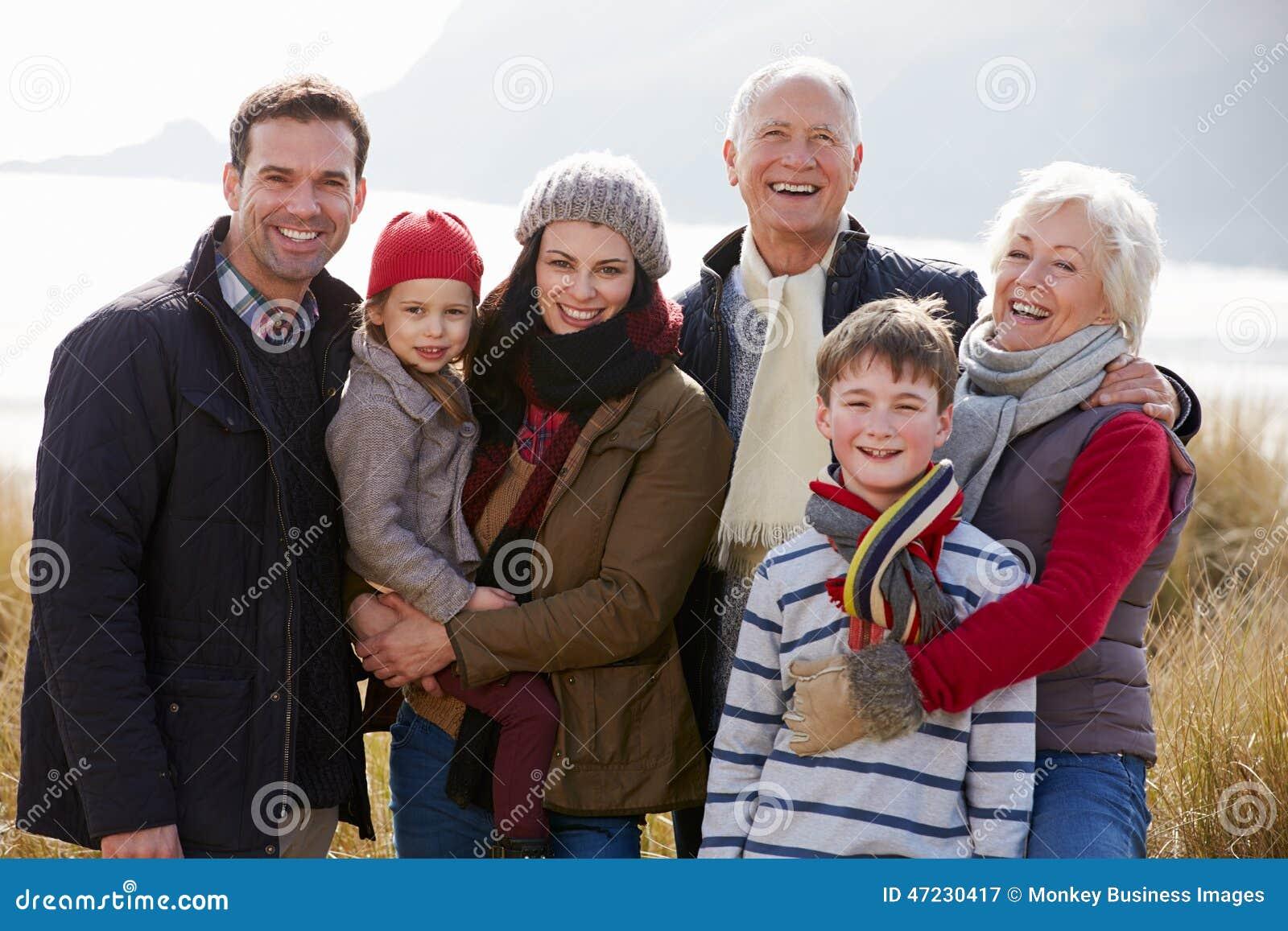 Familia multi de la generación en dunas de arena en la playa del invierno