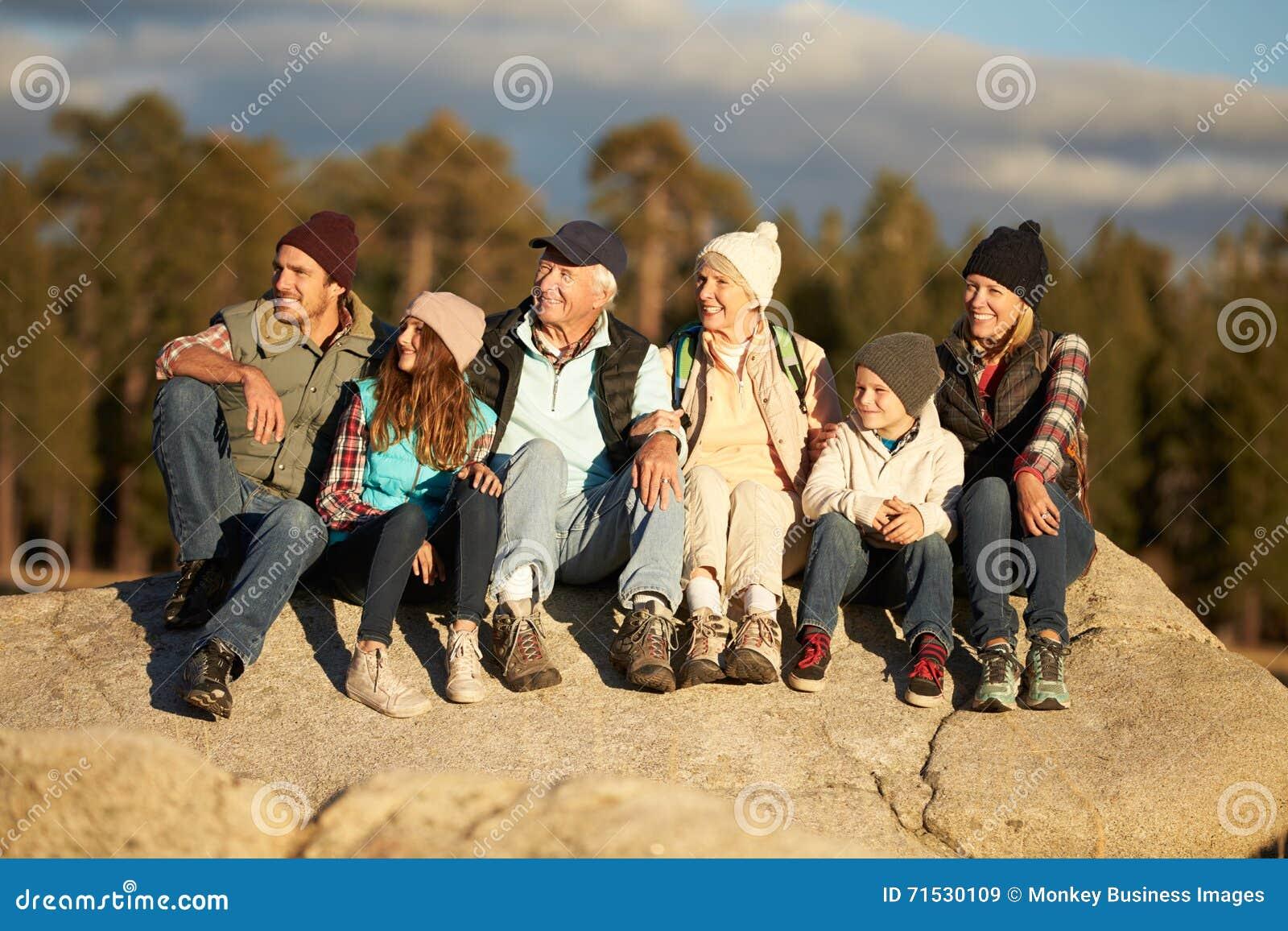 Familia multi de la generación que se sienta en afloramiento rocoso cerca de un bosque
