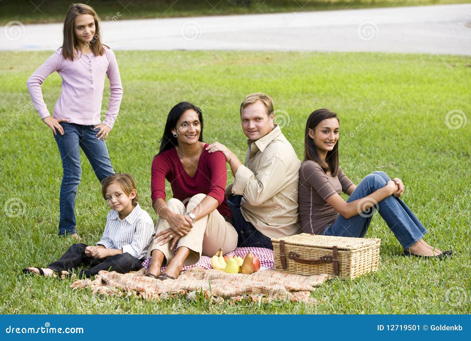 Familia multicultural moderna feliz que disfruta de comida campestre