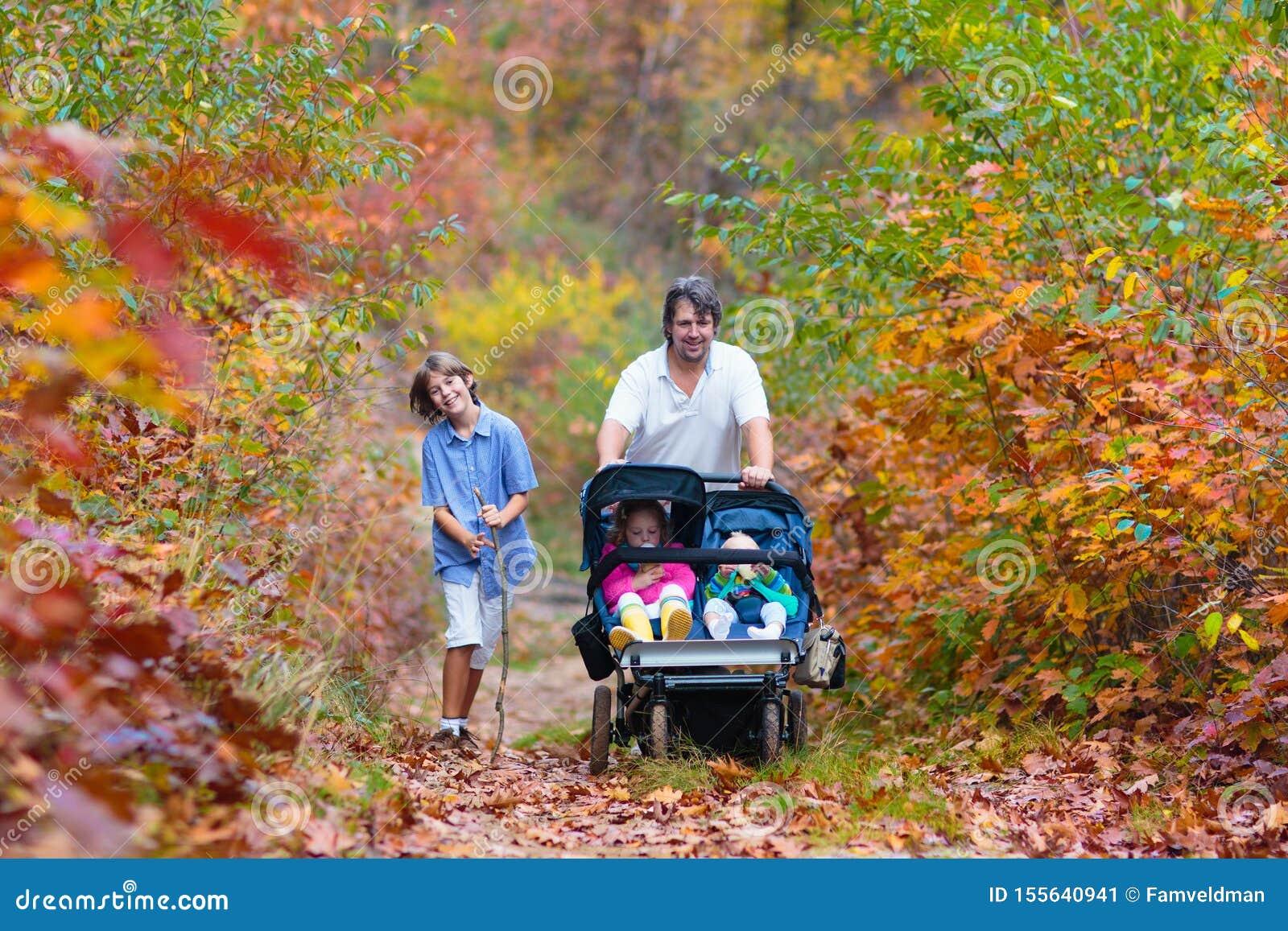 Familia que camina con el cochecito en parque del otoño