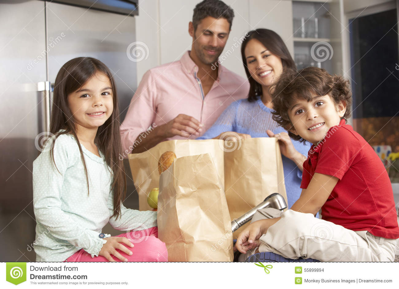 Familia que desempaqueta compras en cocina
