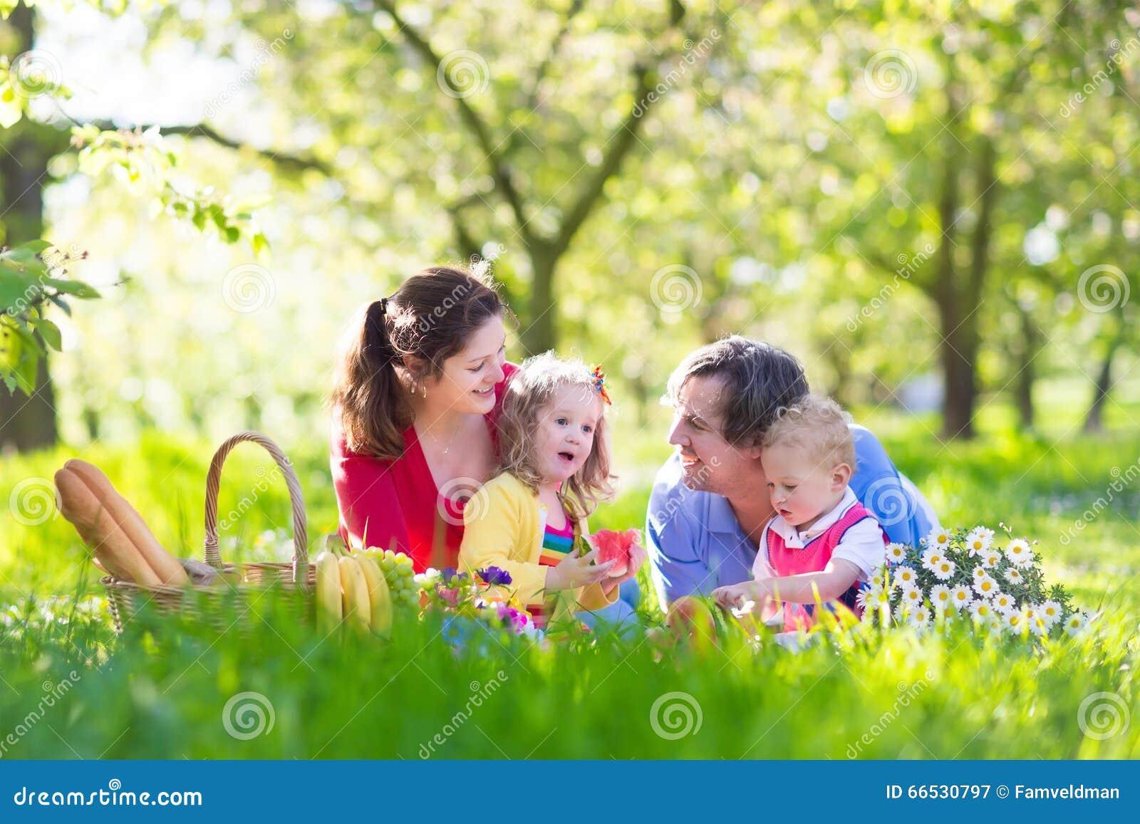 Familia que disfruta de comida campestre en jardín floreciente