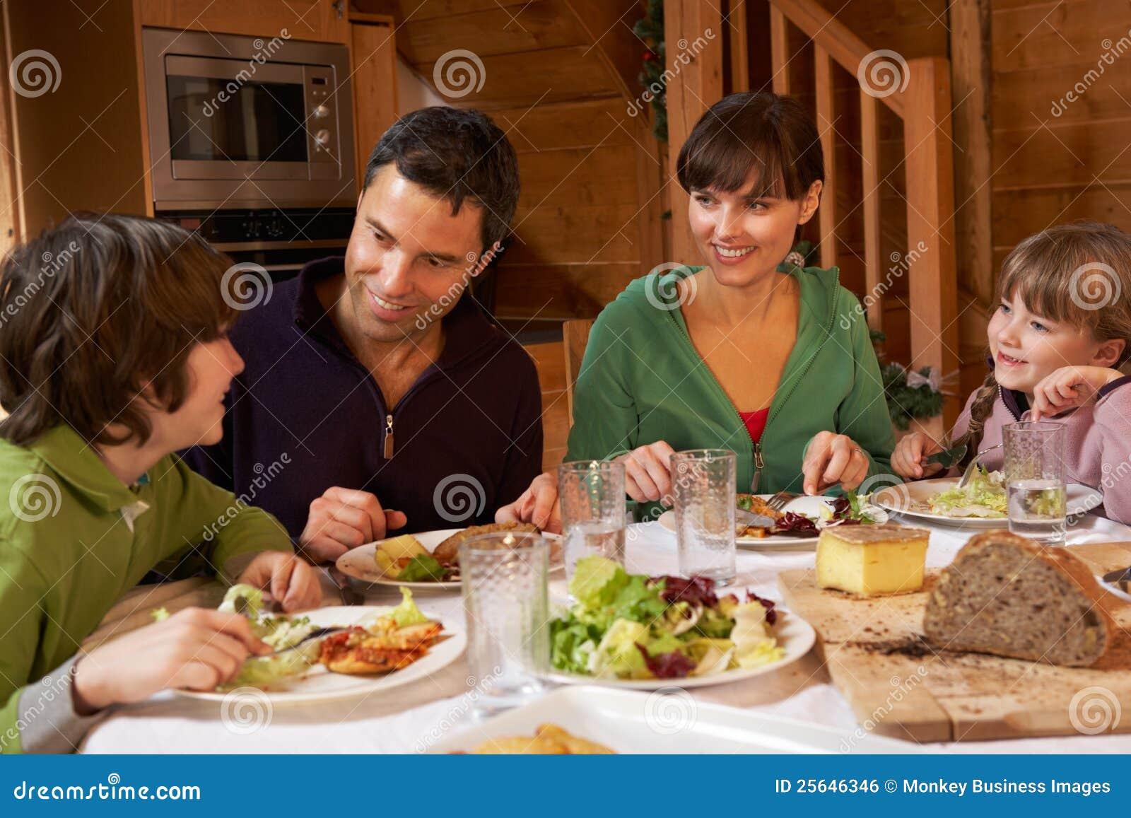 Familia que disfruta de la comida en chalet alpestre junto