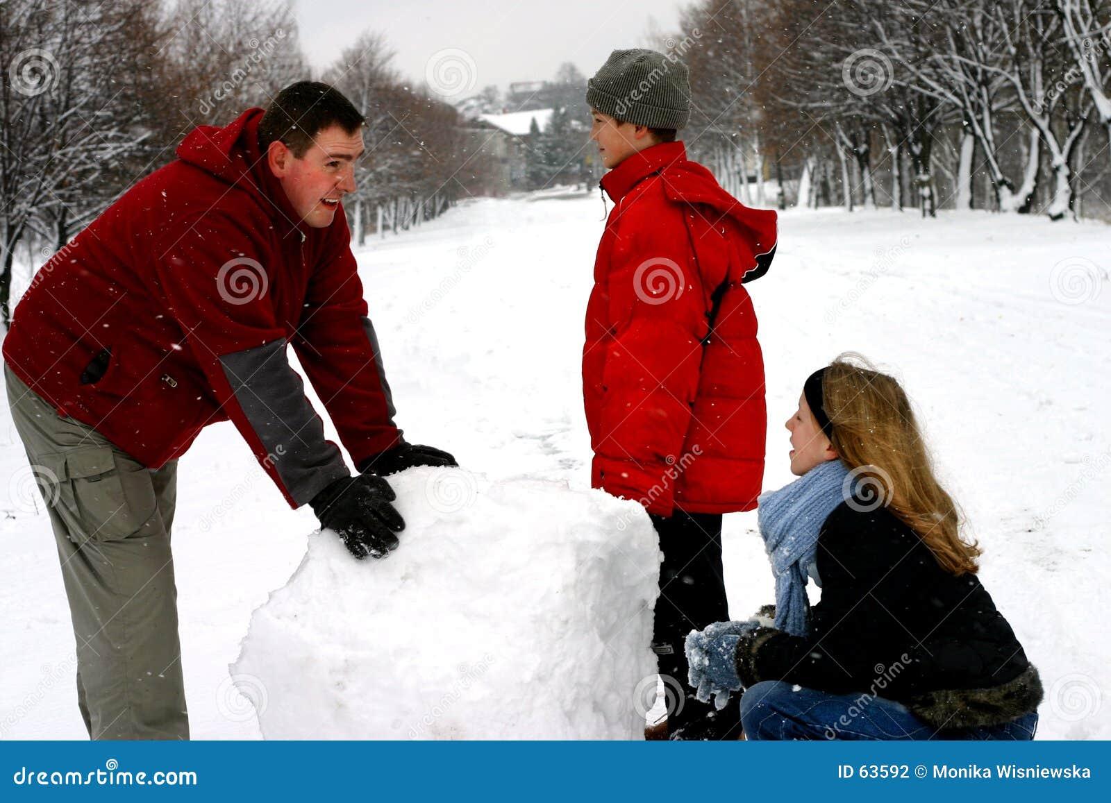Familia que hace el muñeco de nieve