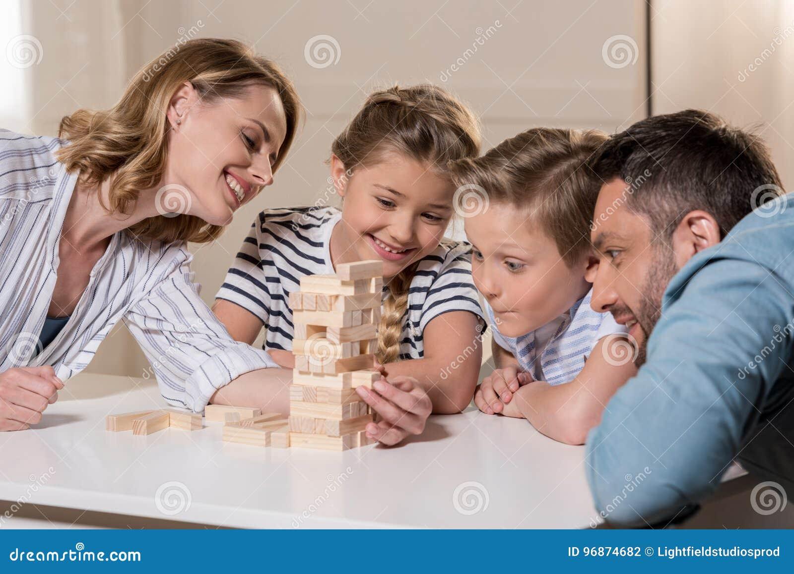 Familia Que Juega Al Juego De Jenga En Casa Junto Foto De Archivo
