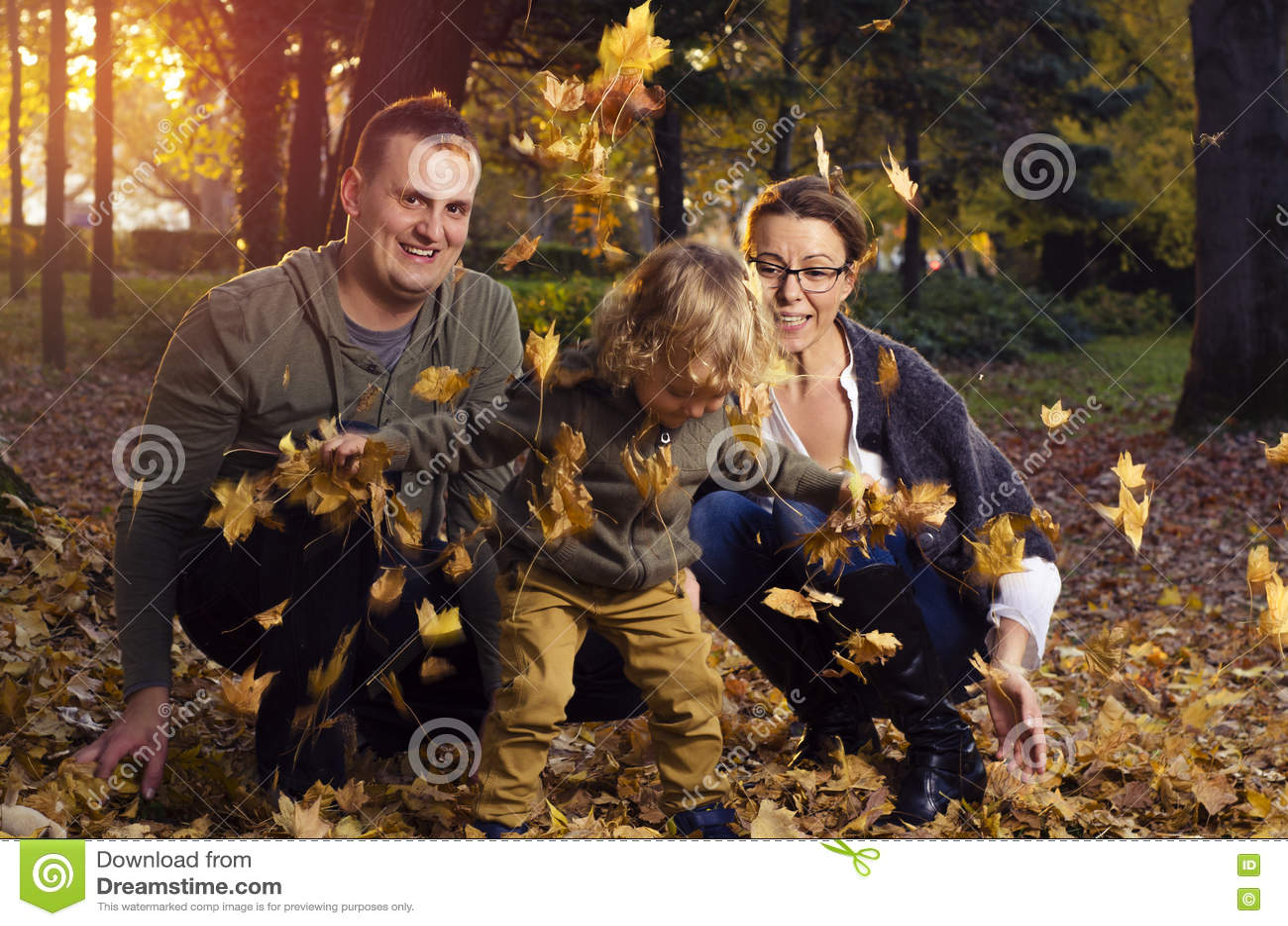Familia que juega en hojas de otoño