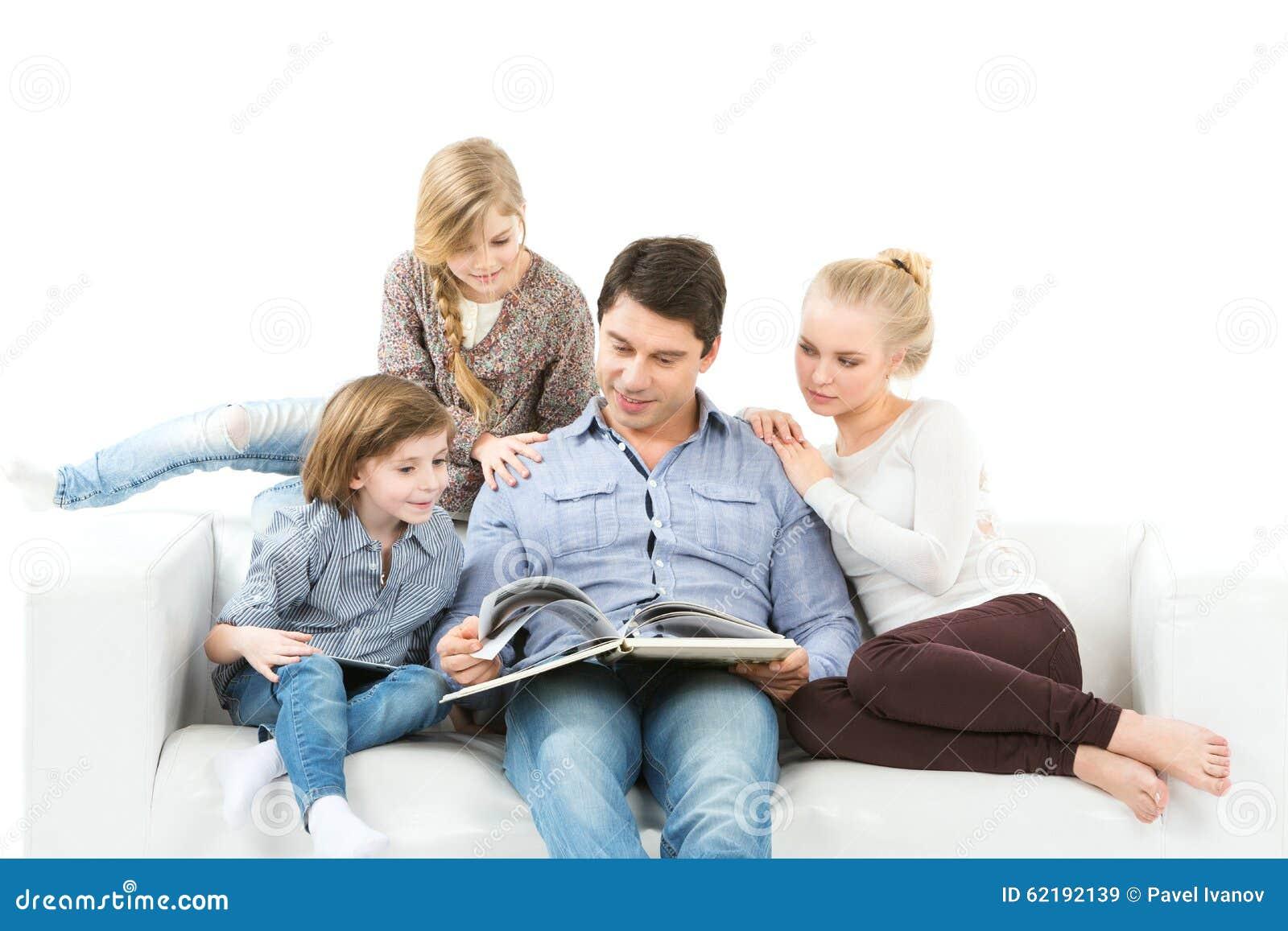 Familia que lee un libro aislado en el fondo blanco