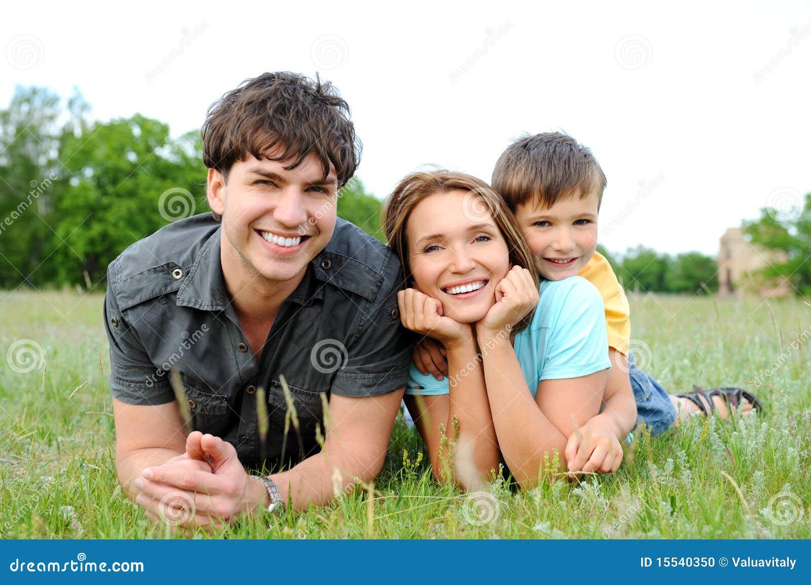 Familia que miente en la hierba verde