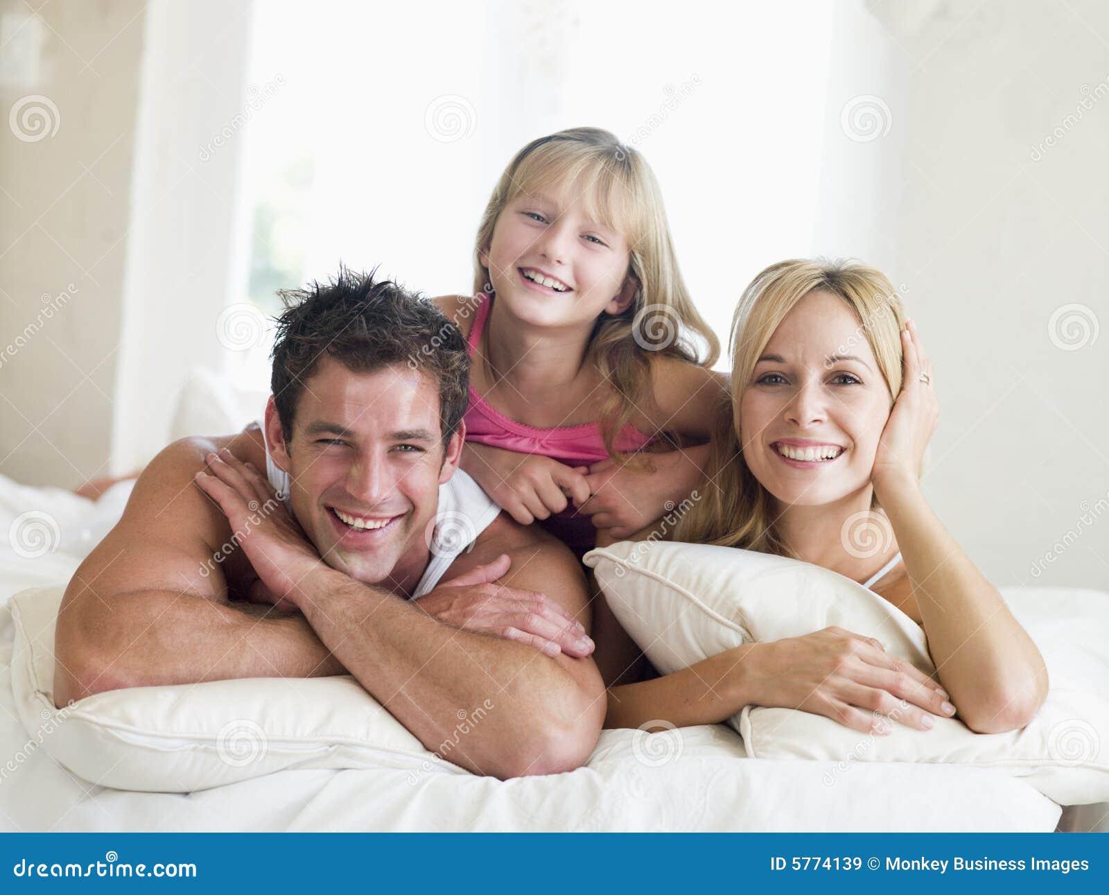 Familia que miente en la sonrisa de la cama