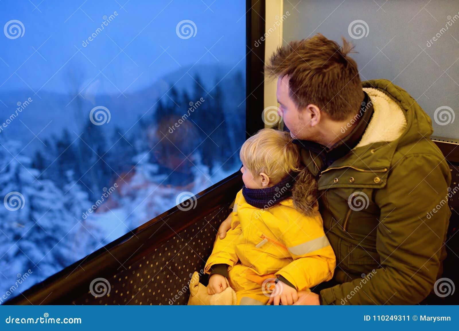 Familia que mira fuera de la ventana del tren durante viaje en ferrocarril de la rueda dentada/ferrocarril de estante en montañas