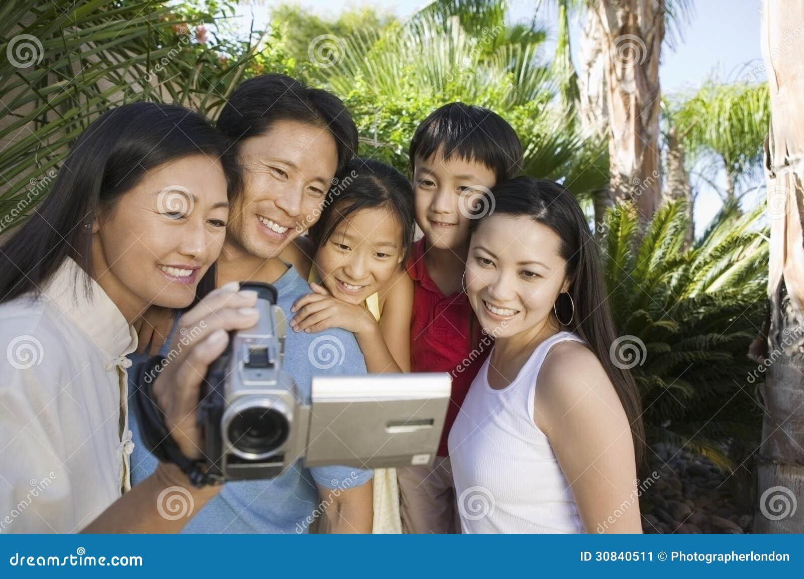 Familia que mira la pantalla de la cámara de vídeo en vista delantera del patio trasero
