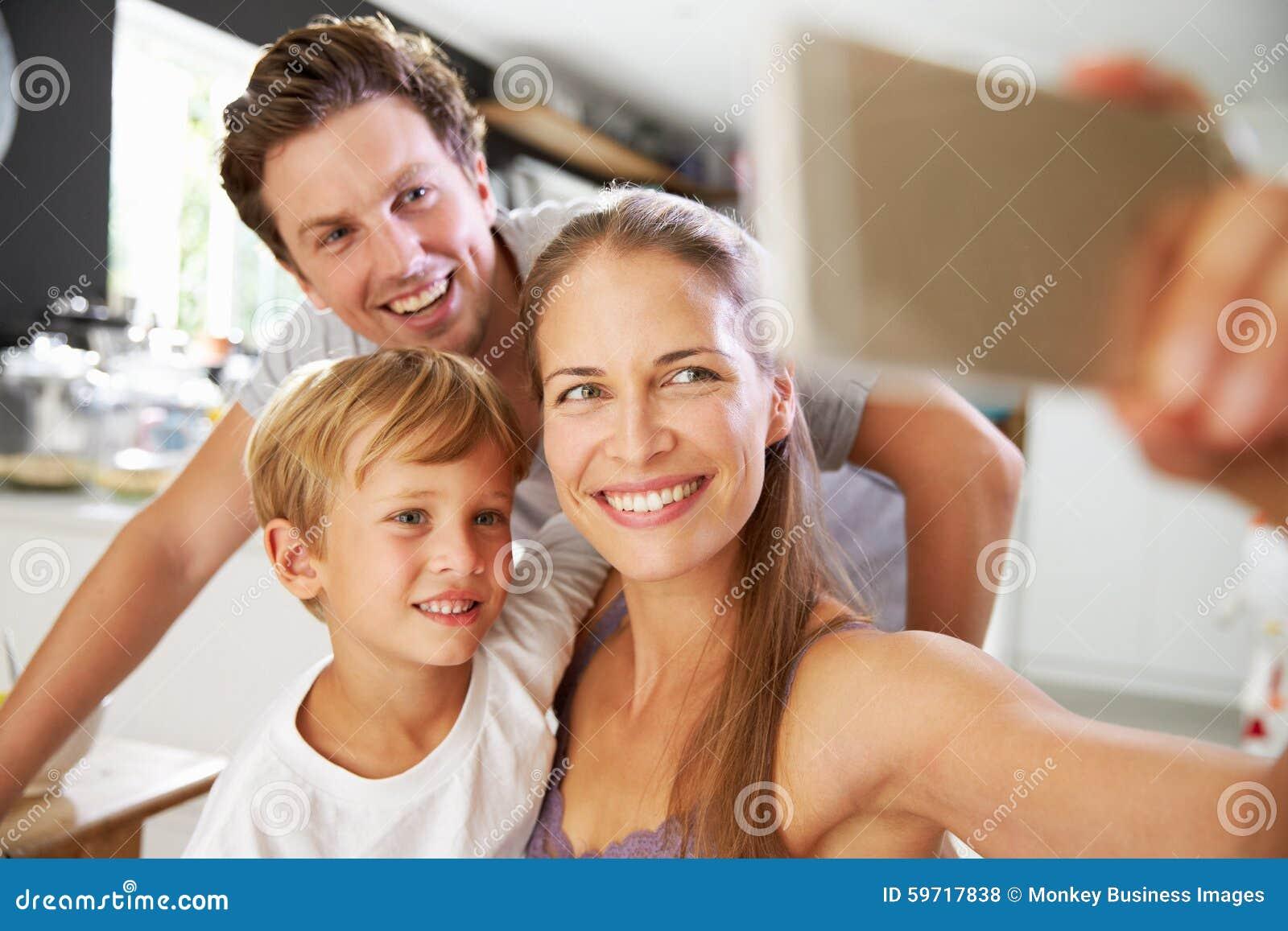 Familia que presenta para Selfie en la mesa de desayuno