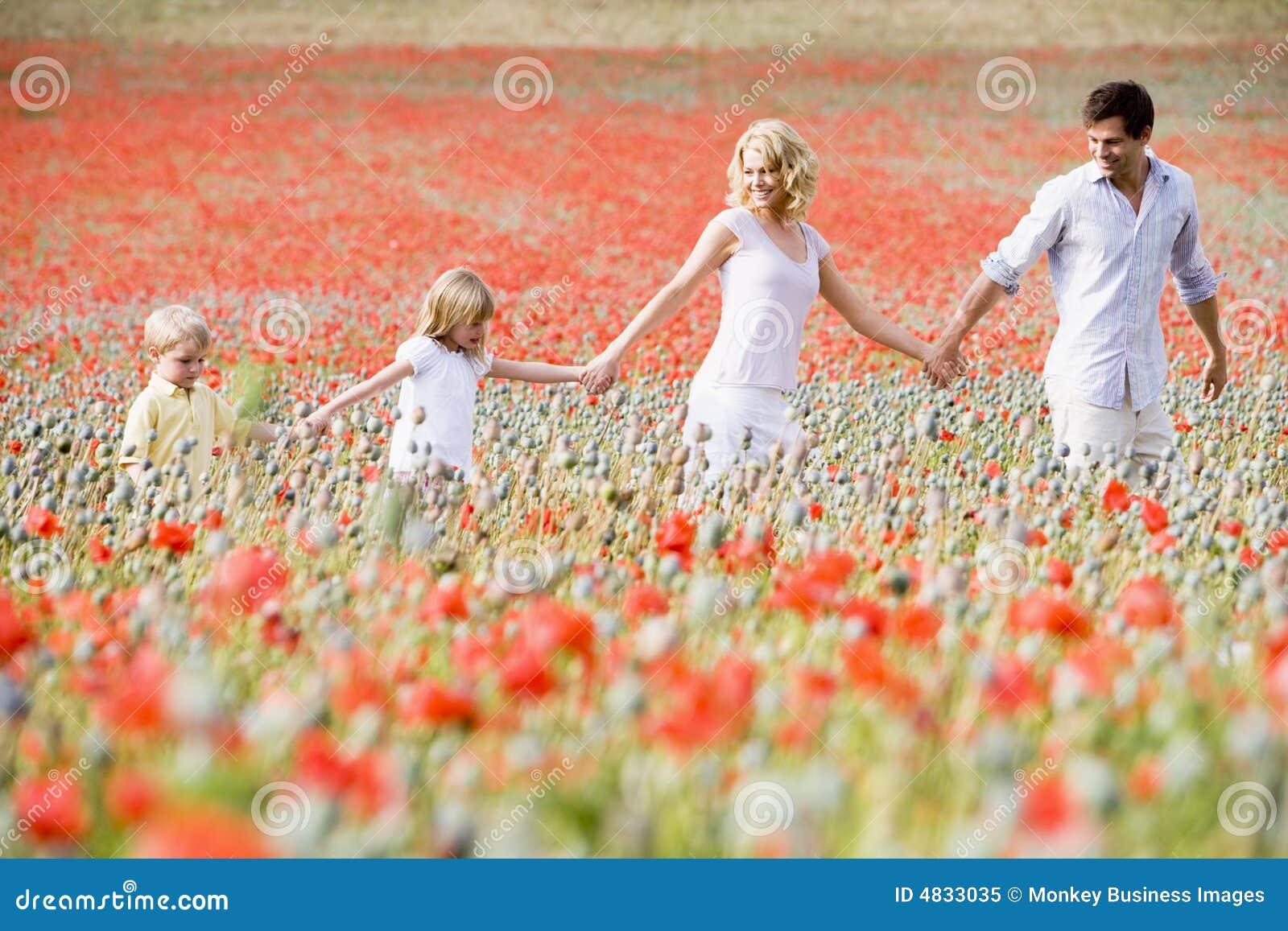 Familia que recorre a través de campo de la amapola