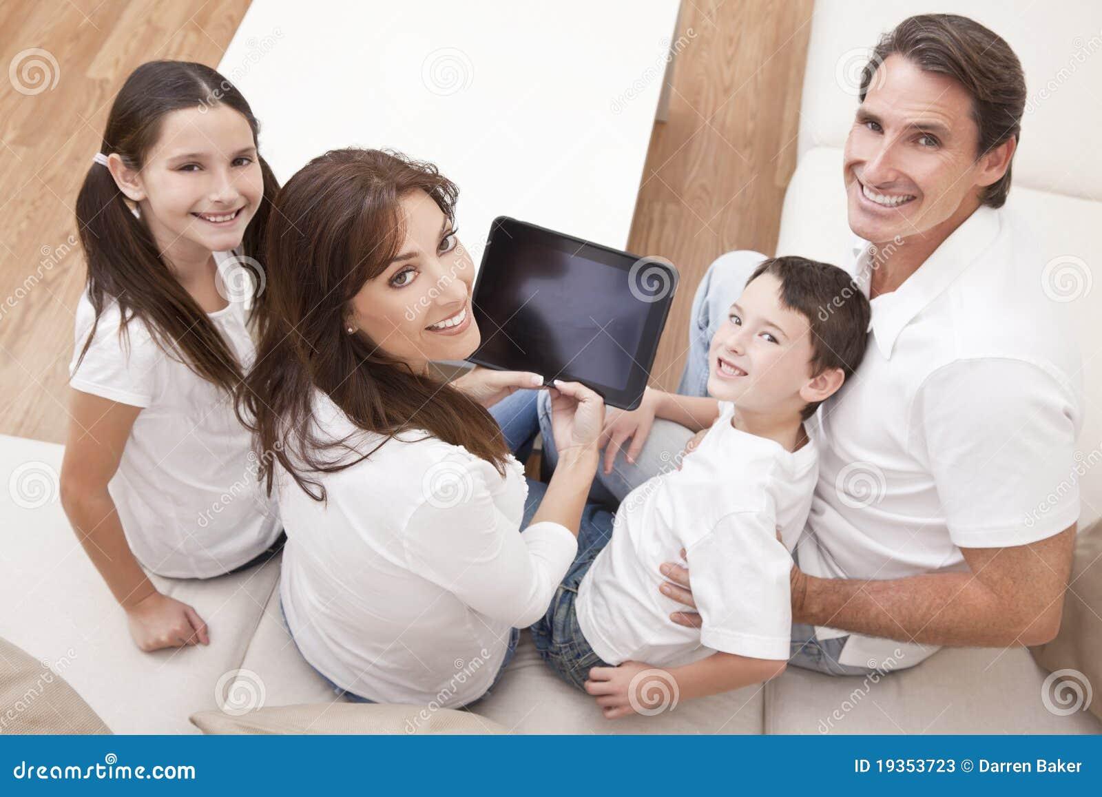 Familia que se divierte usando el ordenador de la tablilla en el país
