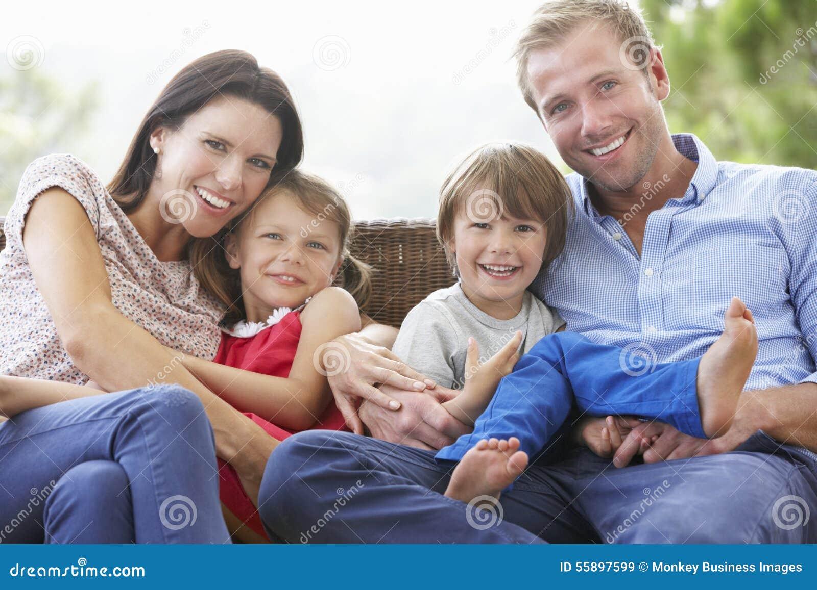 Familia que se sienta en el jardín Seat junto
