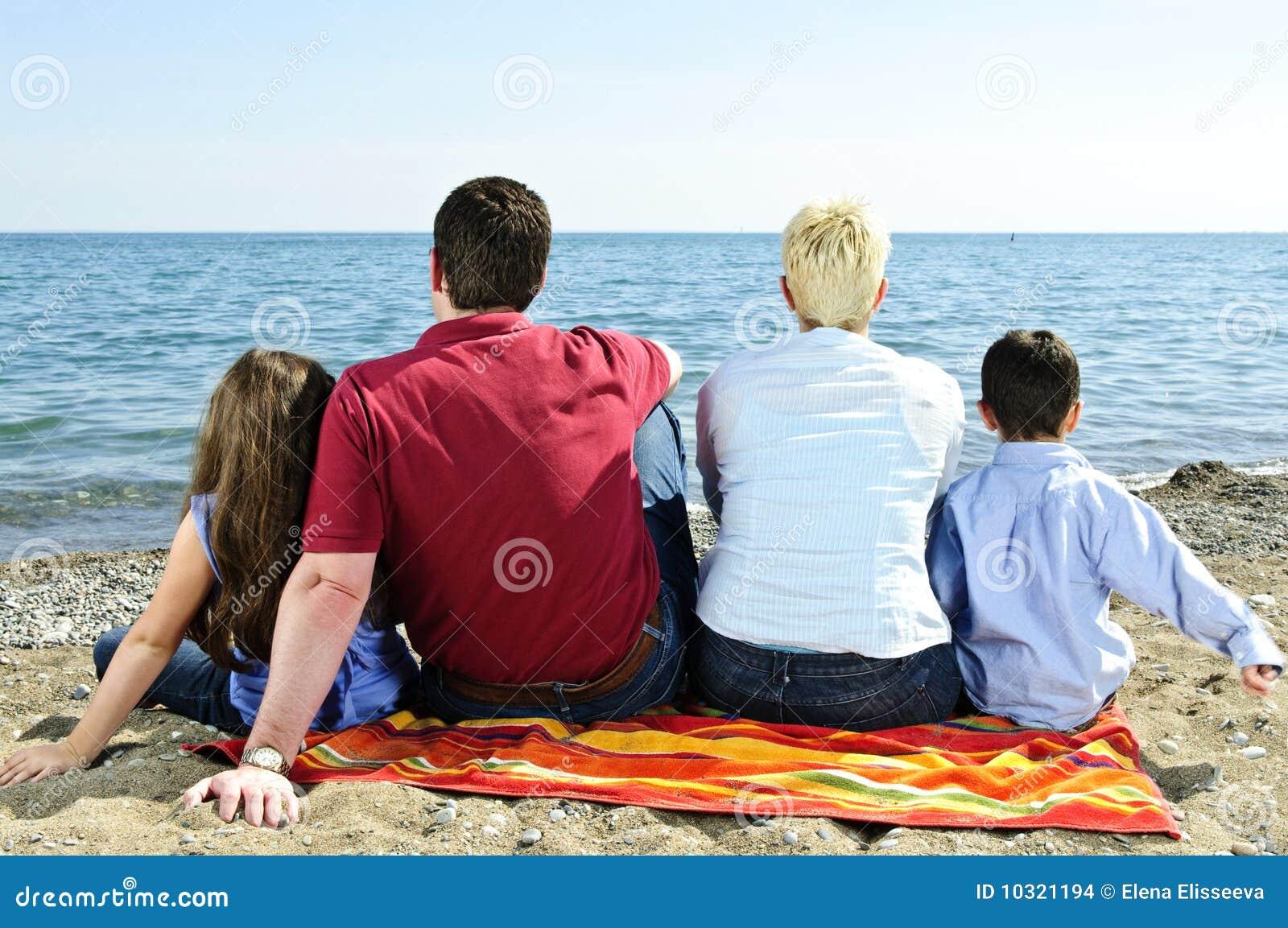 Familia que se sienta en la playa