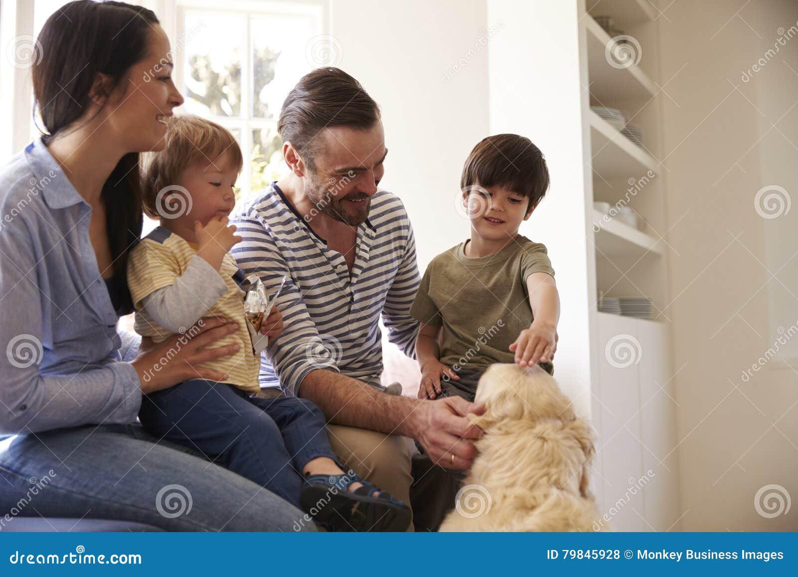 Familia que se sienta en la ventana Seat en casa con golden retriever