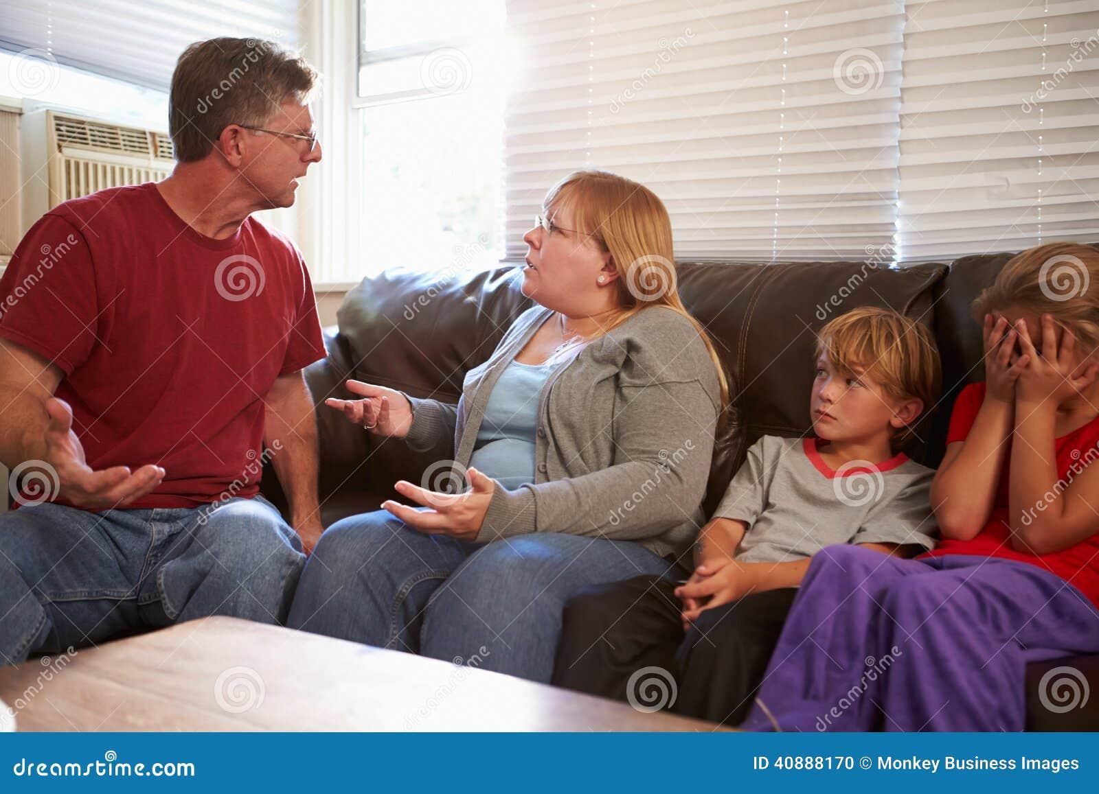 Familia que se sienta en Sofa With Parents Arguing