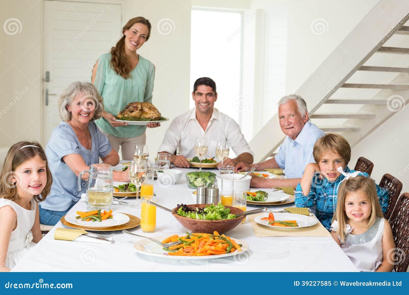 familia que tiene comida en la mesa de comedor foto de