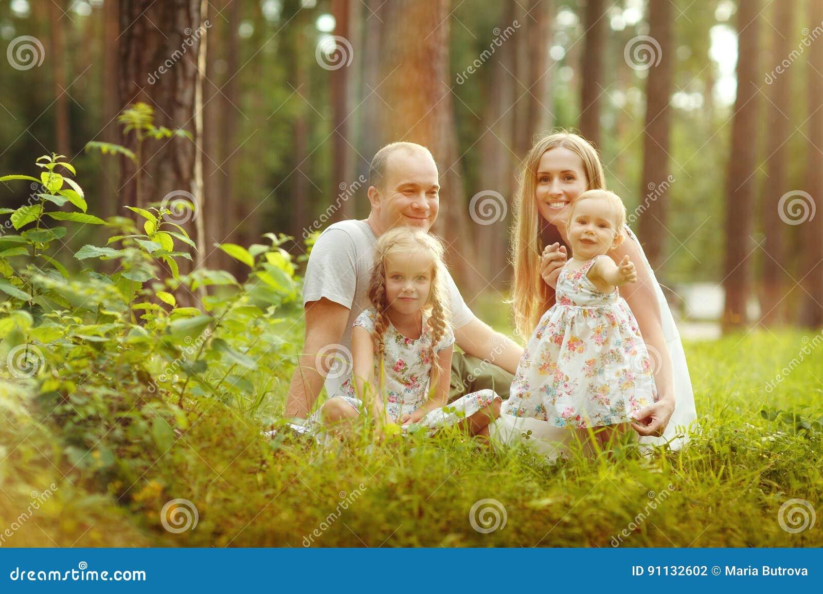 Familia - sentada rubia de la madre, del padre y de dos hijas en un su
