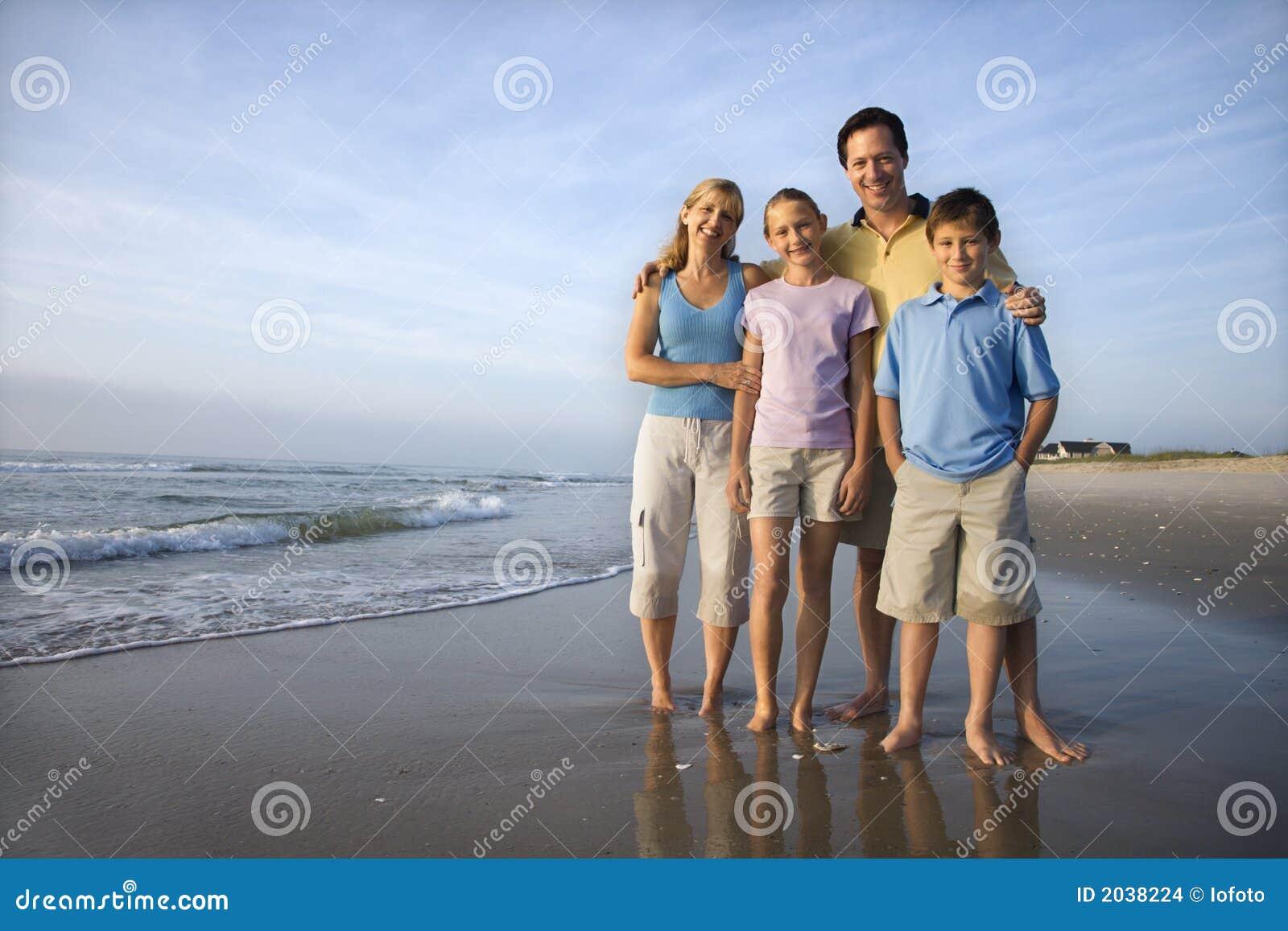 Familia sonriente en la playa.