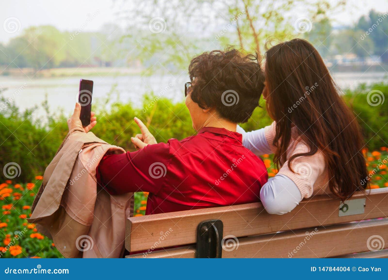 Familia, tecnolog?a y concepto de la gente - hija feliz y madre mayor con el smartphone que se sienta en banco y tomar de parque