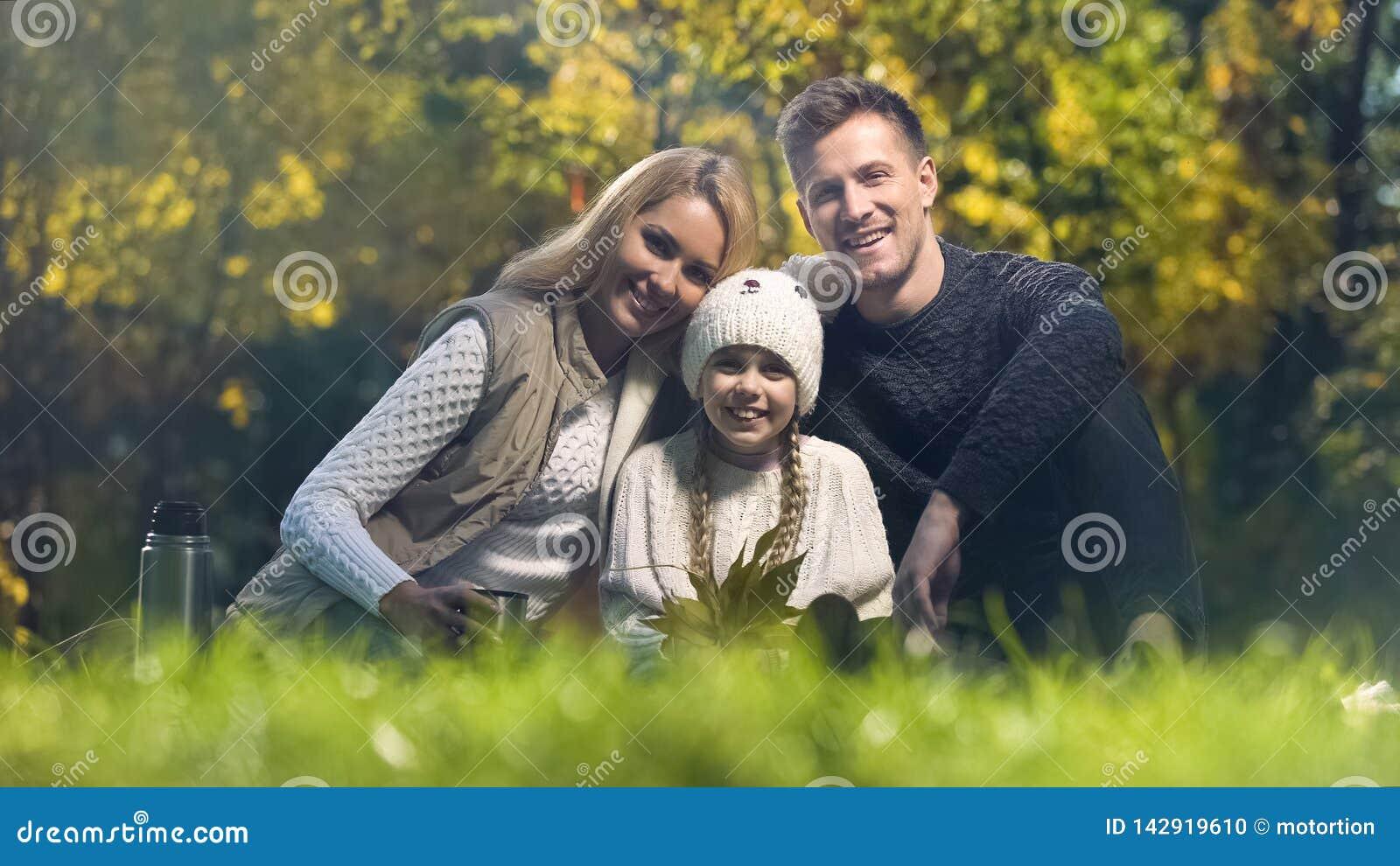 Familia tradicional en comida campestre en parque que sonríe y que mira la cámara, seguro