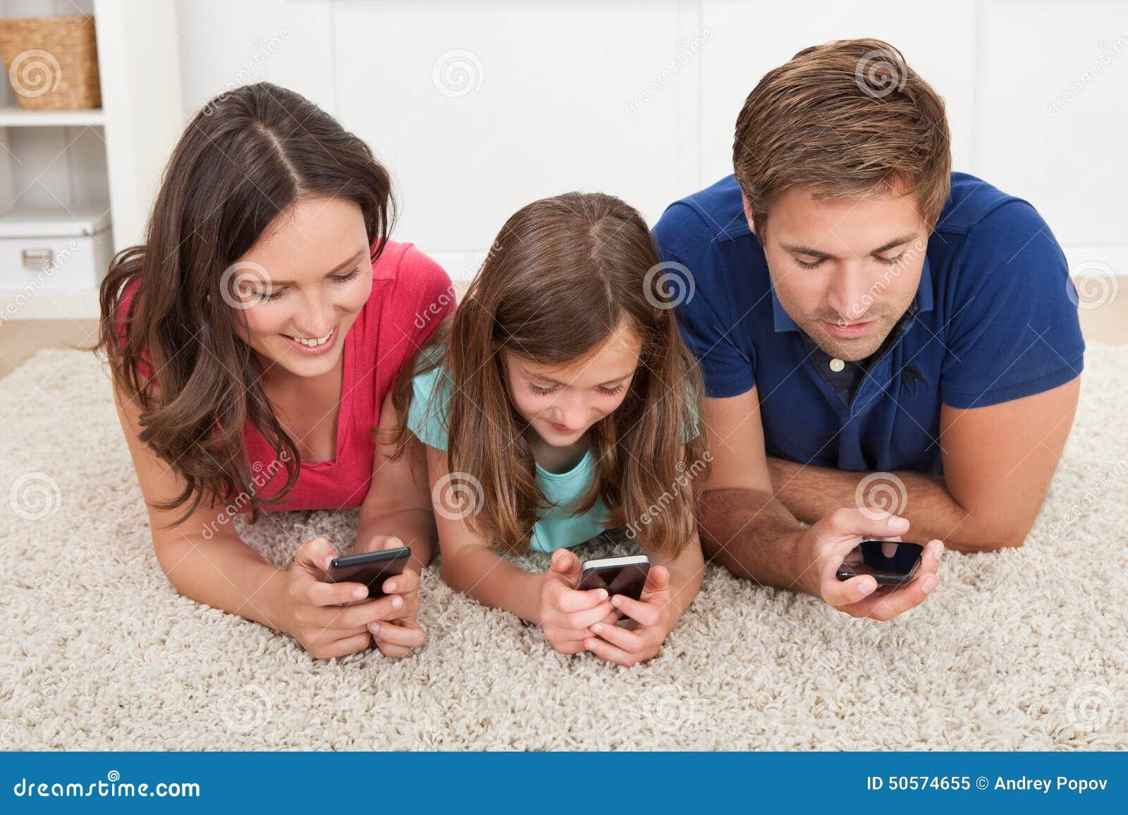 Familia usando los teléfonos elegantes en casa