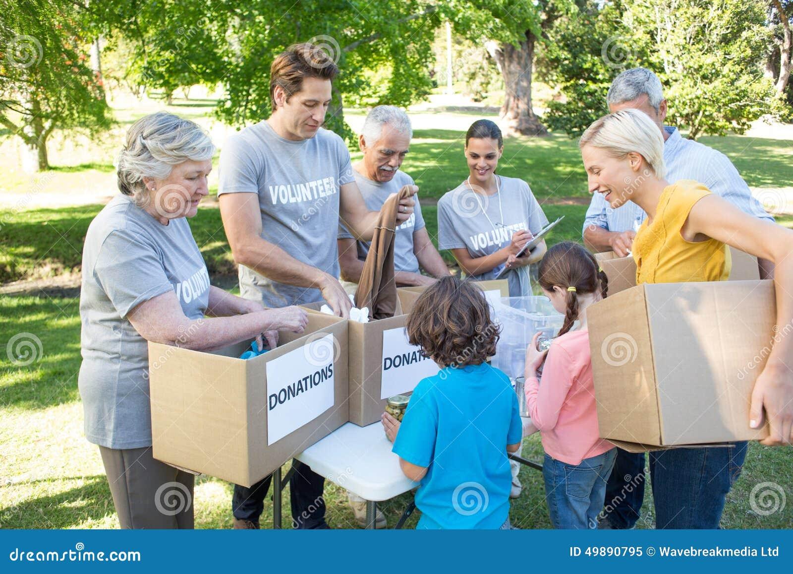 Familia voluntaria feliz que separa las materias de las donaciones