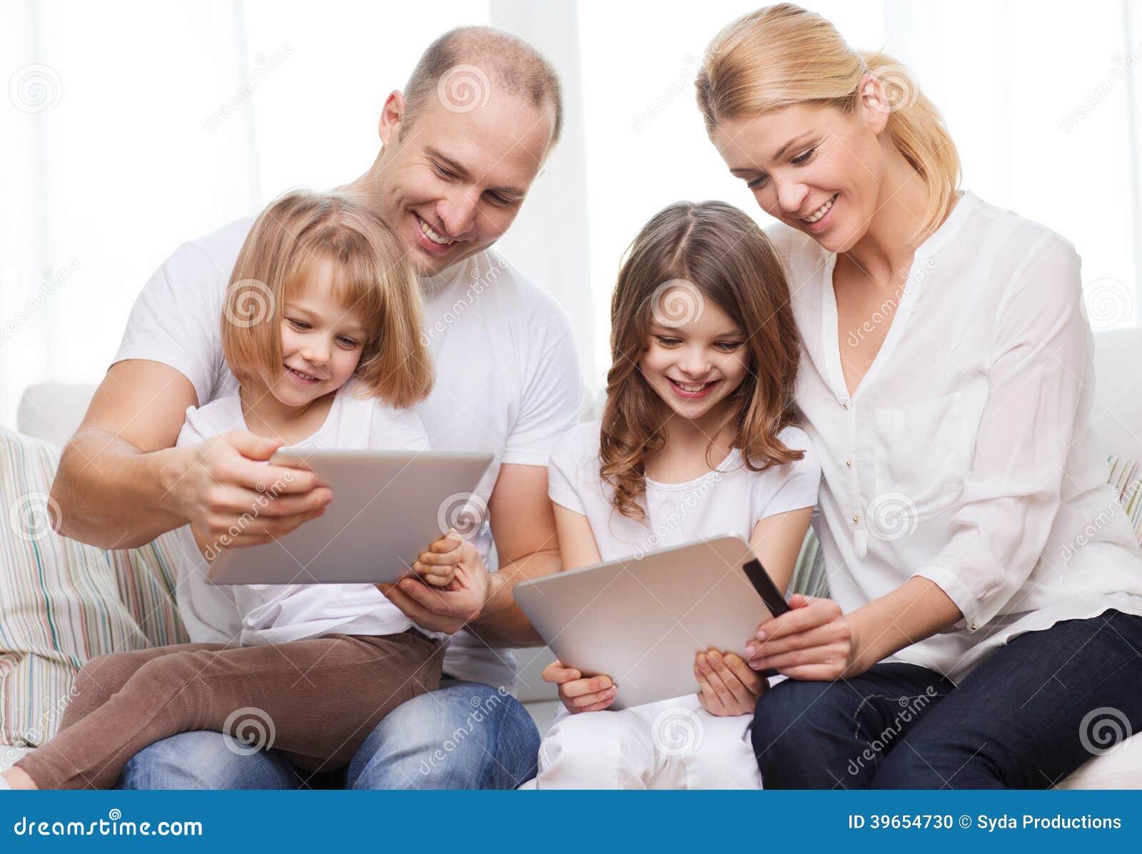 Familia y dos niños con los ordenadores de la PC de la tableta