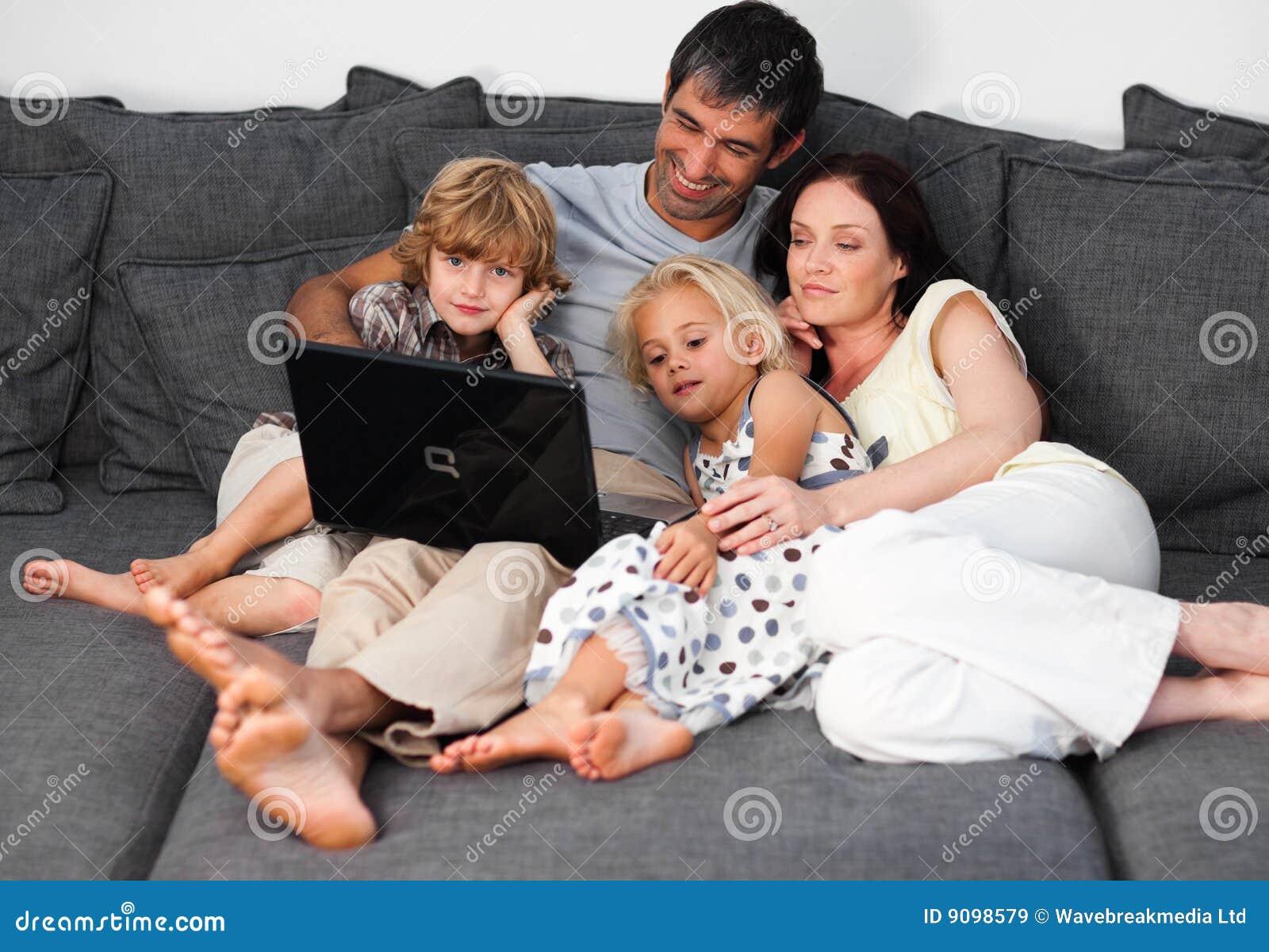Familie auf einem Sofa mit Laptop
