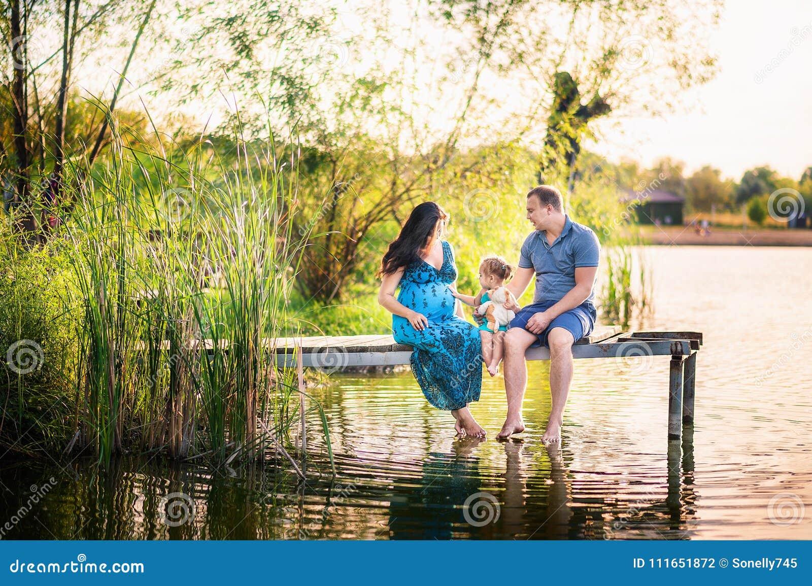 Familie in de zomer op een picknick dichtbij een vijver, water Familievakantie in aard Een kleine dochter met haar vader en een z