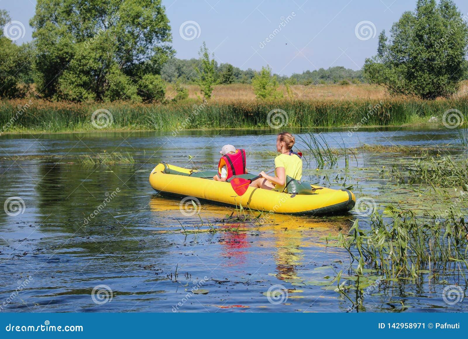 Familie, die auf dem Fluss Kayak fährt Wenig Junge mit seinem mothe