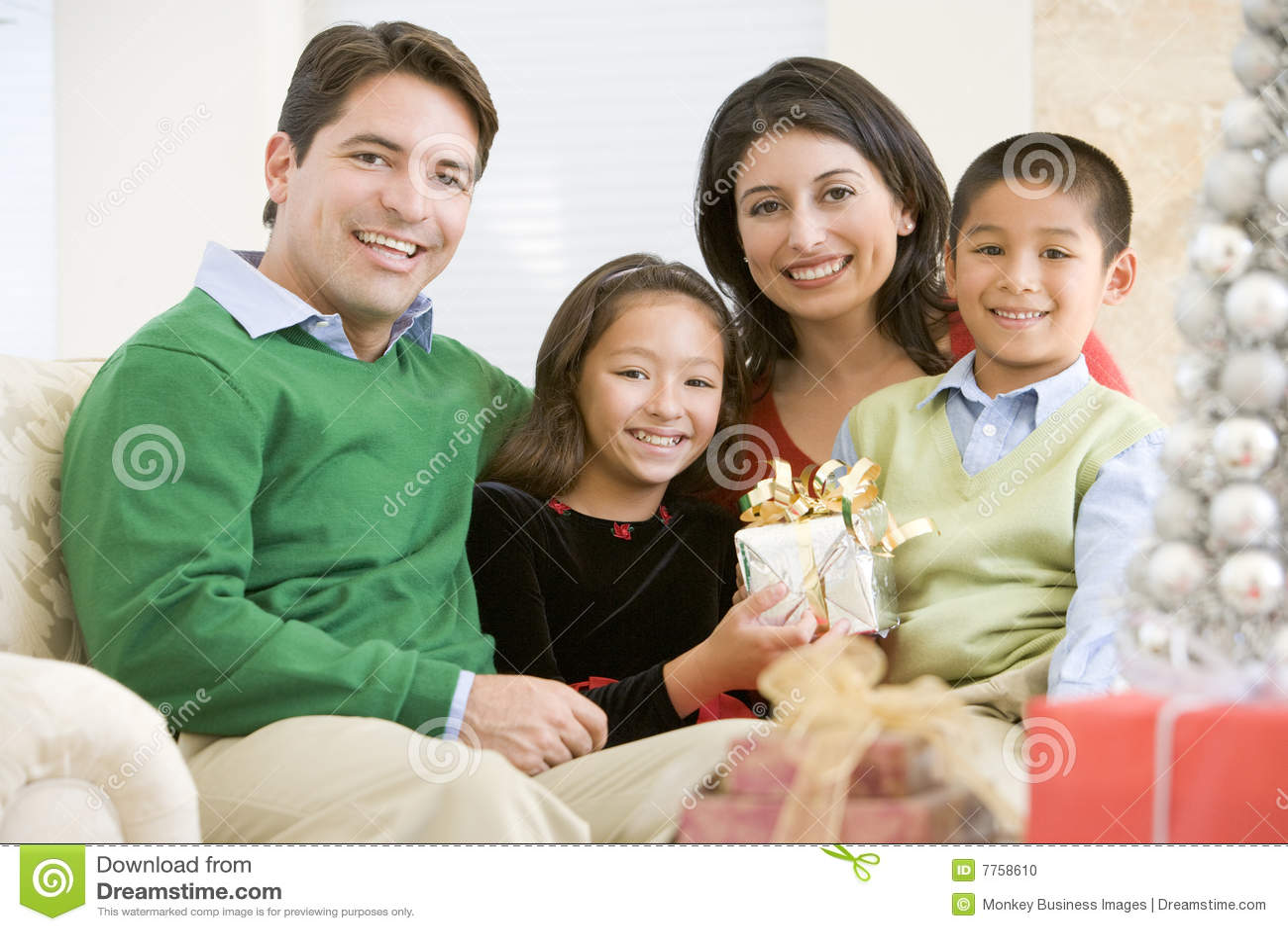 Familie, die auf dem Sofa anhält ein Weihnachtsgeschenk sitzt