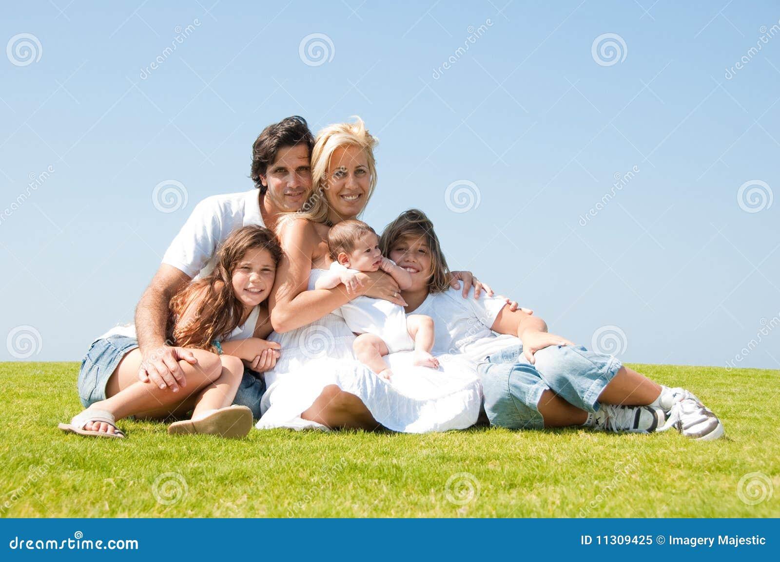 Familie, die auf einem Gras sitzt