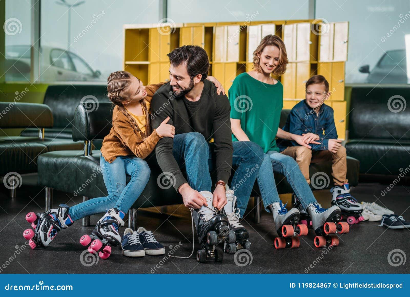Familie, die auf Sofa vor dem Eislauf in Rollschuhe stillsteht