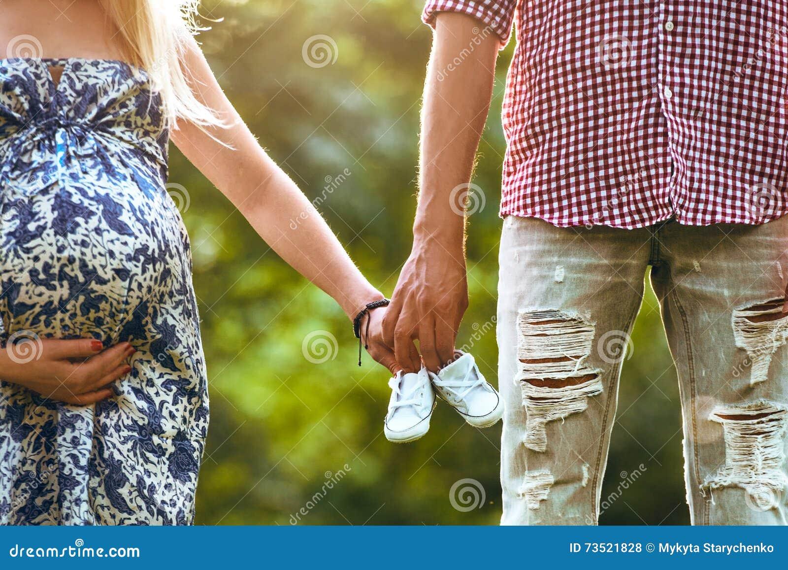 Familie, die Babyschuhe in den Händen zusammenhalten und Stellung, die der Sommer parken Frau ist schwanger