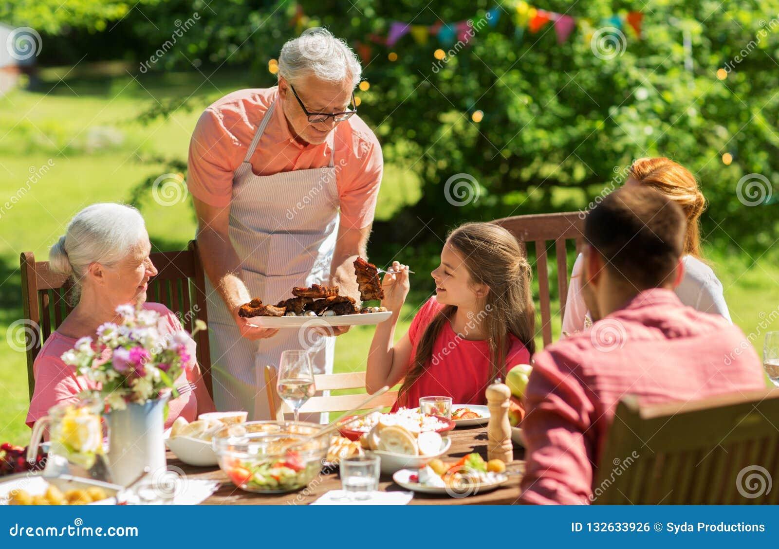 Familie die diner of barbecue hebben bij de zomertuin