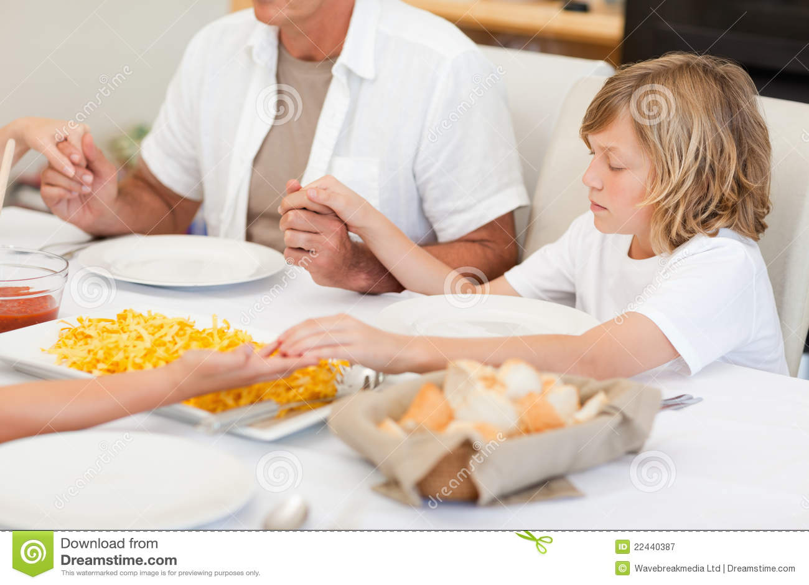 Familie die een gebed zegt vóór diner