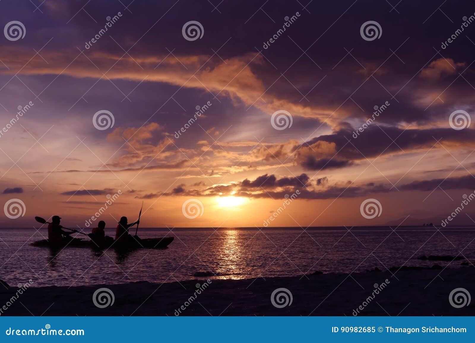 Familie die een kajak paddelen door het overzees