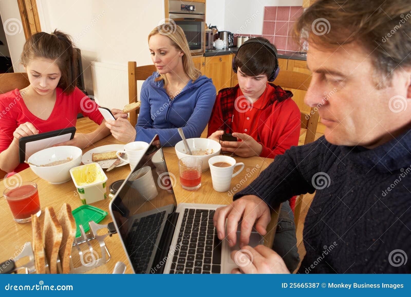 Familie die Gadgets gebruikt terwijl het Eten van Ontbijt