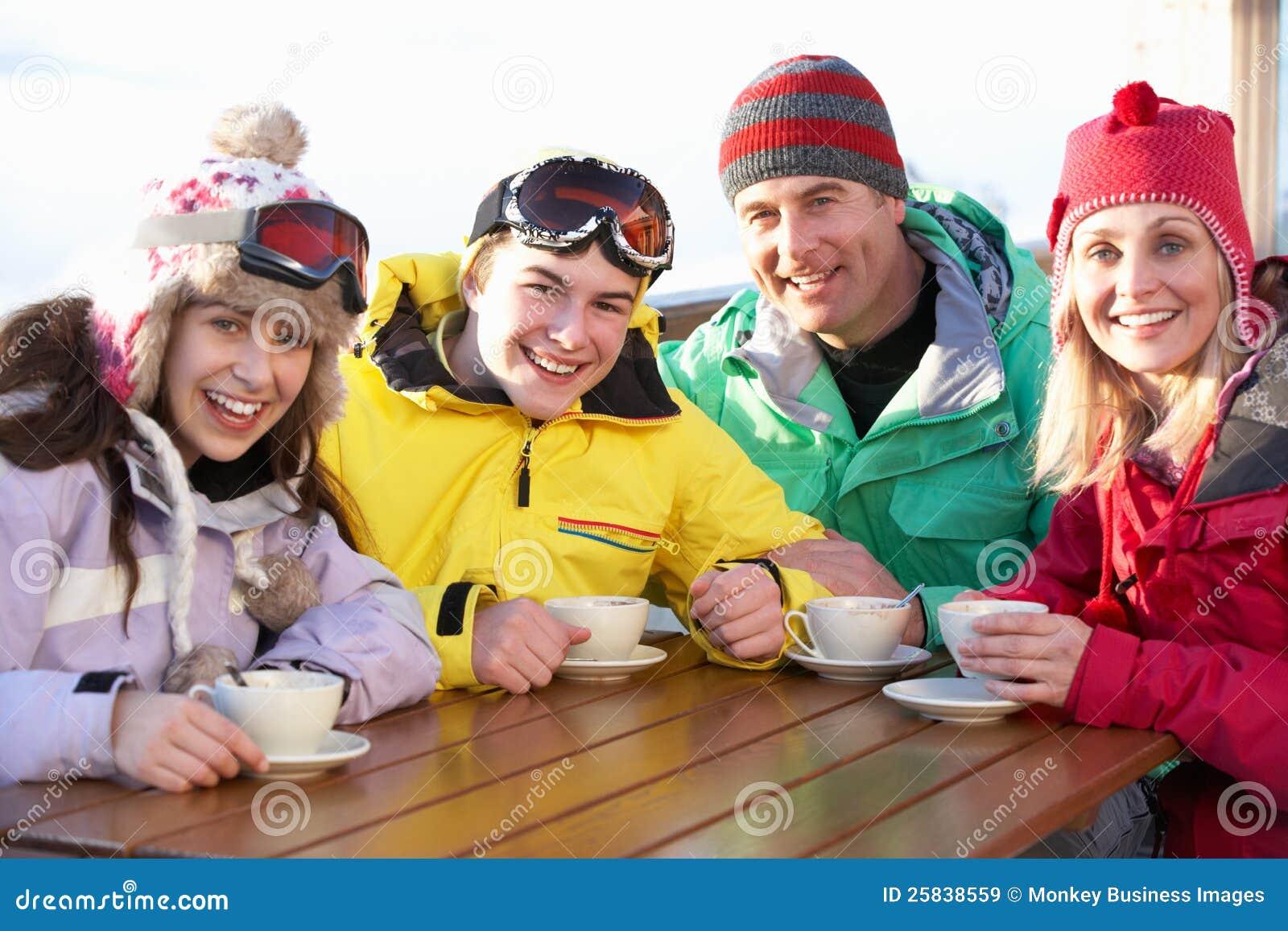 Familie, die heißes Getränk im Kaffee am Skiort genießt