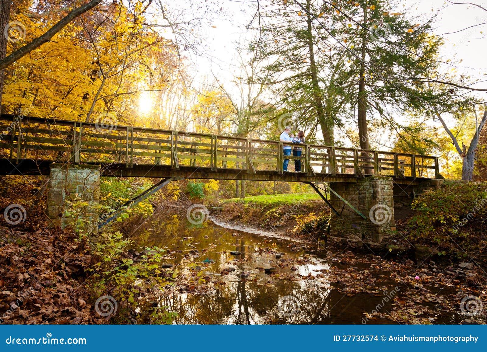 Familie, die Herbst-Farben auf einer Park-Brücke genießt