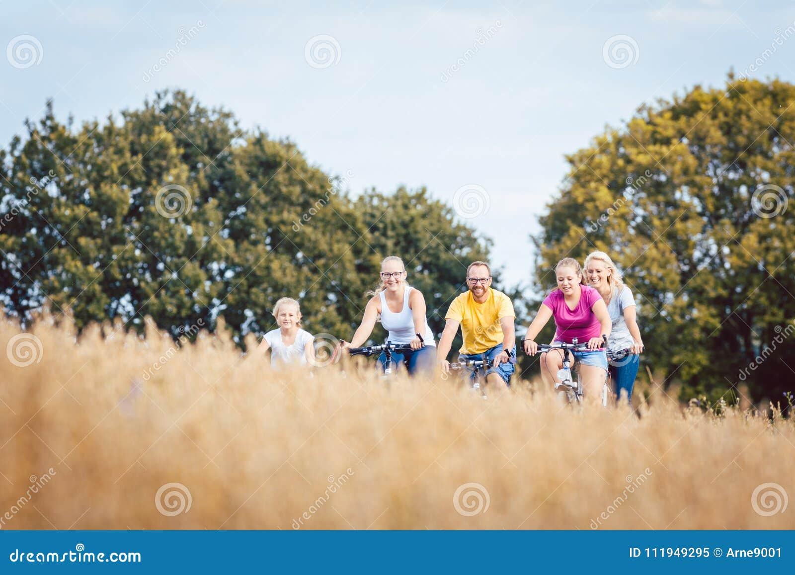 Familie die hun die fietsen berijden boven een korrelgebied worden geschoten