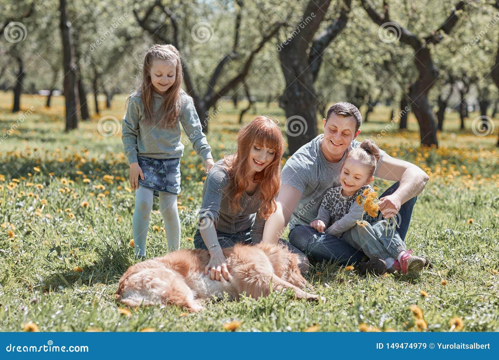 Familie, die ihr Haustier f?r einen Weg streichelt