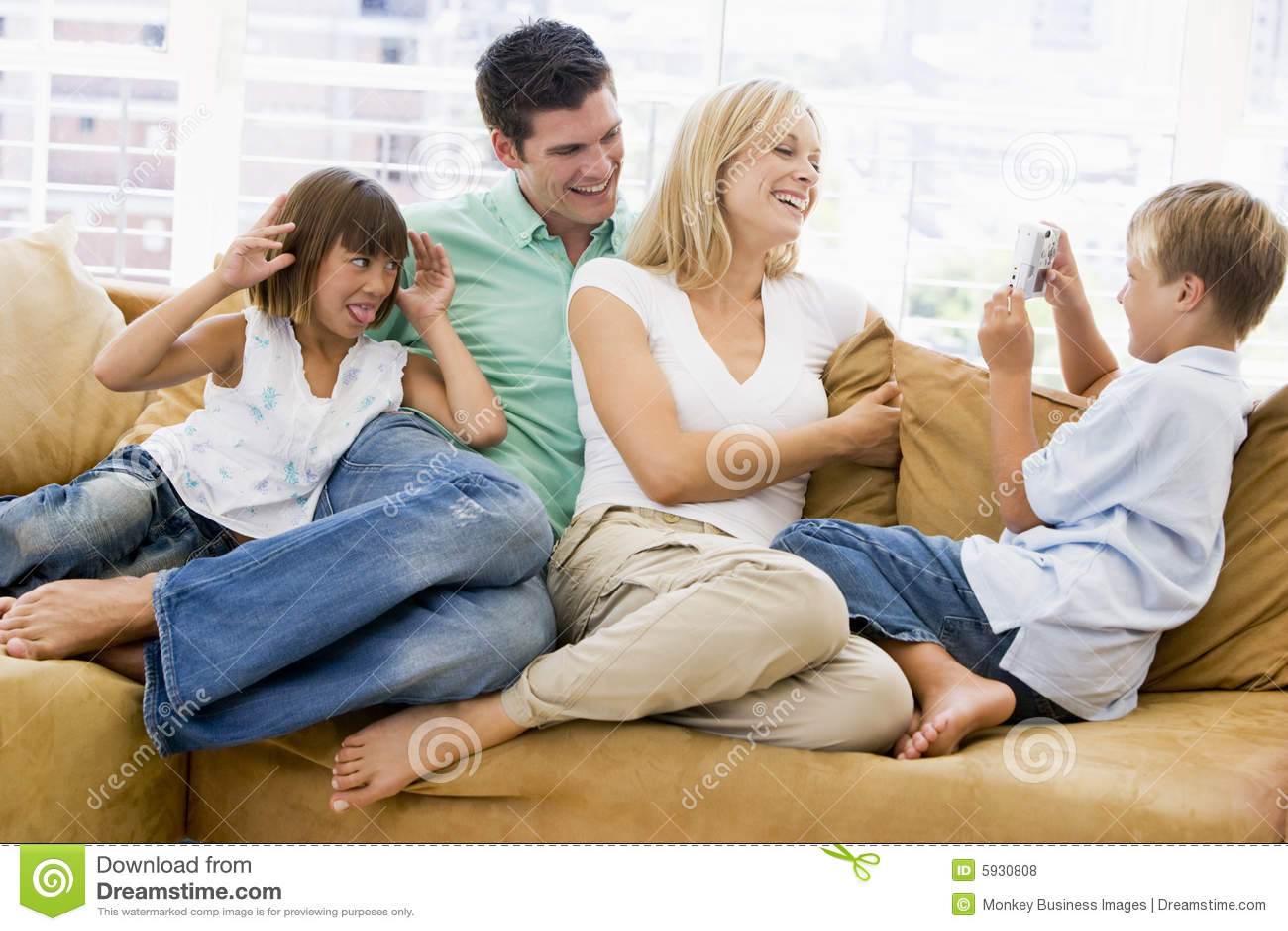 Familie, Die Im Wohnzimmer Mit Digitalkamera Sitzt Stockfoto - Bild ...
